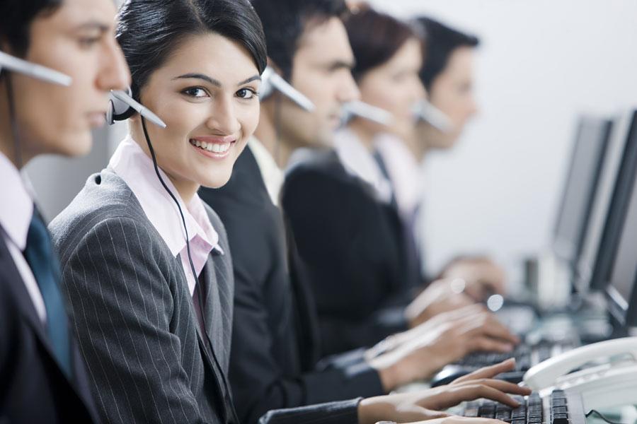 personas trabajando en un call center con ordenadores